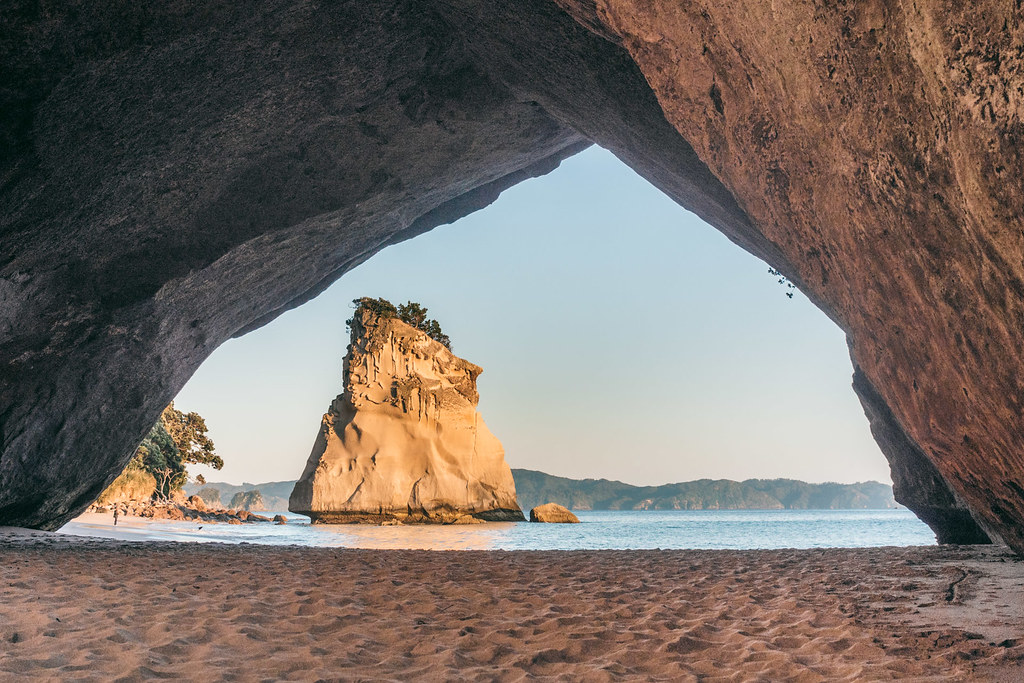 A photo taken from inside a cave towards the sea. A rock standing up from the sea can be seen through the walls of the cave.