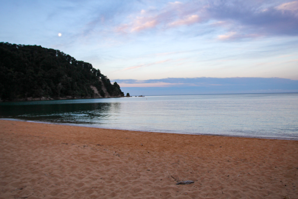 An image of a beach and sunset, with the moon rising on the left above some cliffs