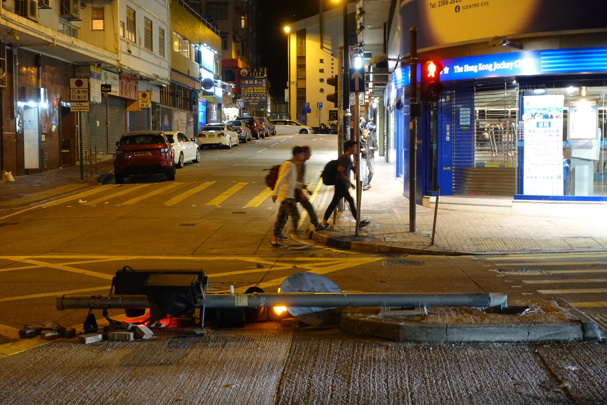 行人經過倒在馬路上的紅綠燈。(攝影:張智琦)