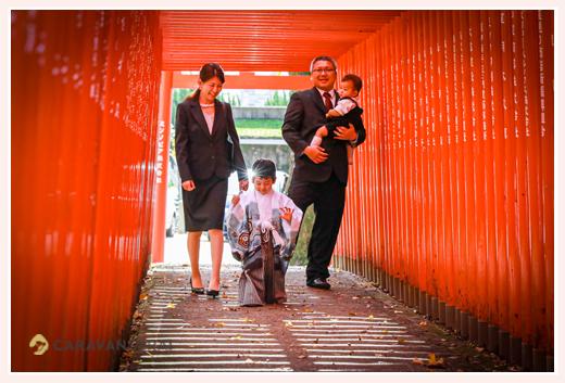 七五三 赤い鳥居の下を歩く家族の写真