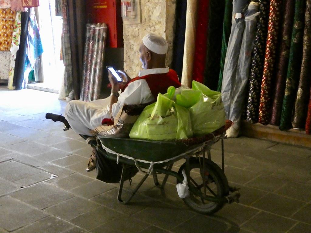 Souq Waqif porter taking a break in wheelbarrow