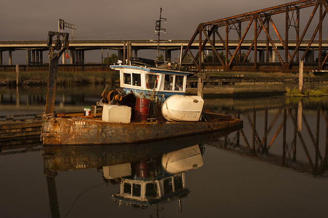 Old abandoned tug boat in industrial marina