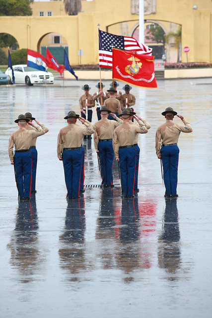 U.S. Marine Corps drill instructors salute the national ensign during a graduation ceremony.