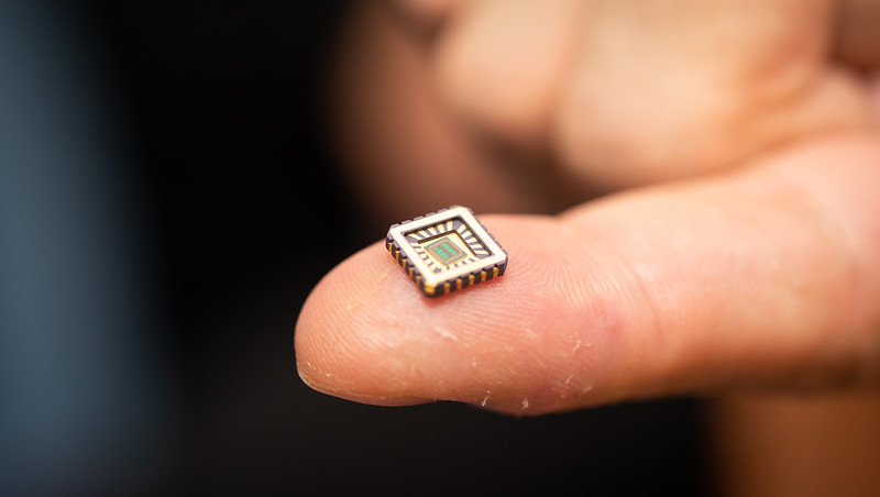 One of the tiny chips in its protective casing on the end of a fingertip.