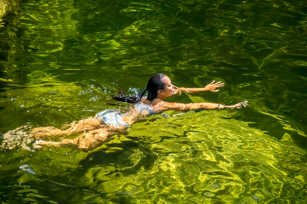Oriental woman swimming in Mossman River