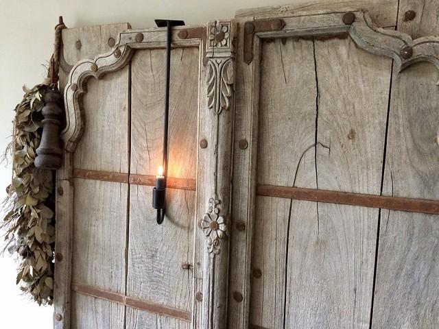 Oude houten deur met hangkandelaar en groene toef