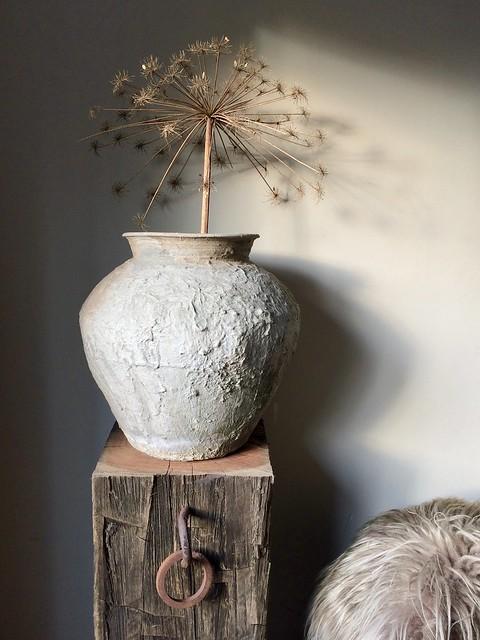 Kruik met berenklauw op houten zuil