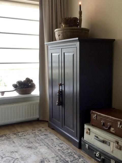 Zwarte kast oude koffers vloerkleed landelijk