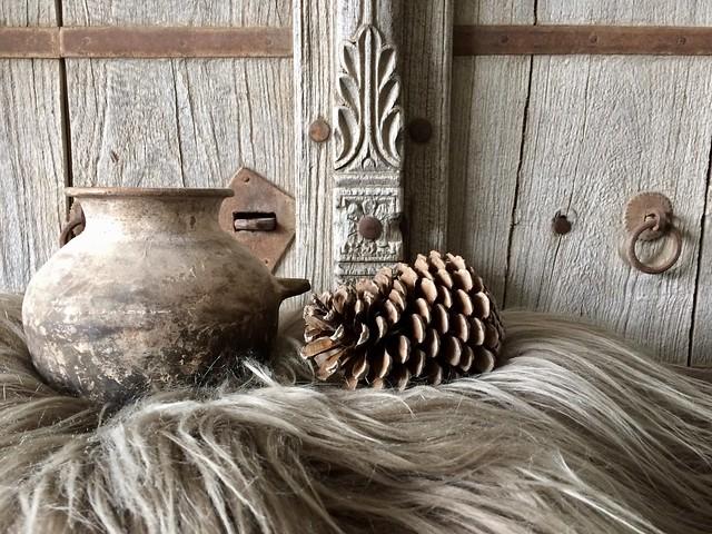 Oud kruikje schapenvacht oude deur dennenappel