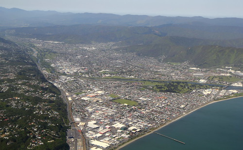 <p>Home to around 107,000 people, Lower Hutt is New Zealand's seventh-largest city.  It is built on and around the lower alluvial fan of the Hutt River, which is bounded on its western side by the active Wellington Fault.  The fault separates the flood plain from the western hill suburbs.  The flood plain narrows into the distance towards the Taita Gorge, which separates Lower Hutt from...you guessed it...Upper Hutt.<br /> <br /> The prominent range along the right-hand (east) side of the photo is the Remutaka Range, which in turn passes northwards into the Tararua Range.<br /> <br /> The haze in the sky is smoke and dust from the Australian bush fires, which has been blown more than 2000 km across the Tasman Sea.</p>
