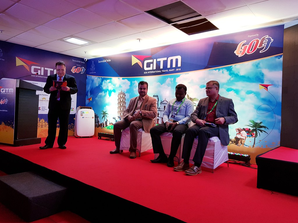 A panel with four men discussing the Goa tourism, on a red stage.