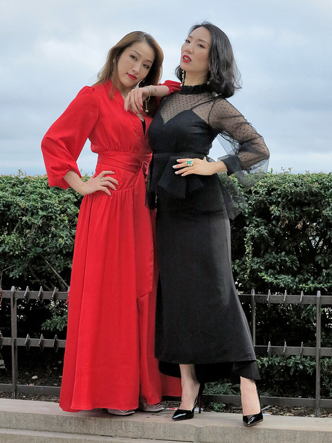 The two Asian models pose together with their red and black evening dresses
