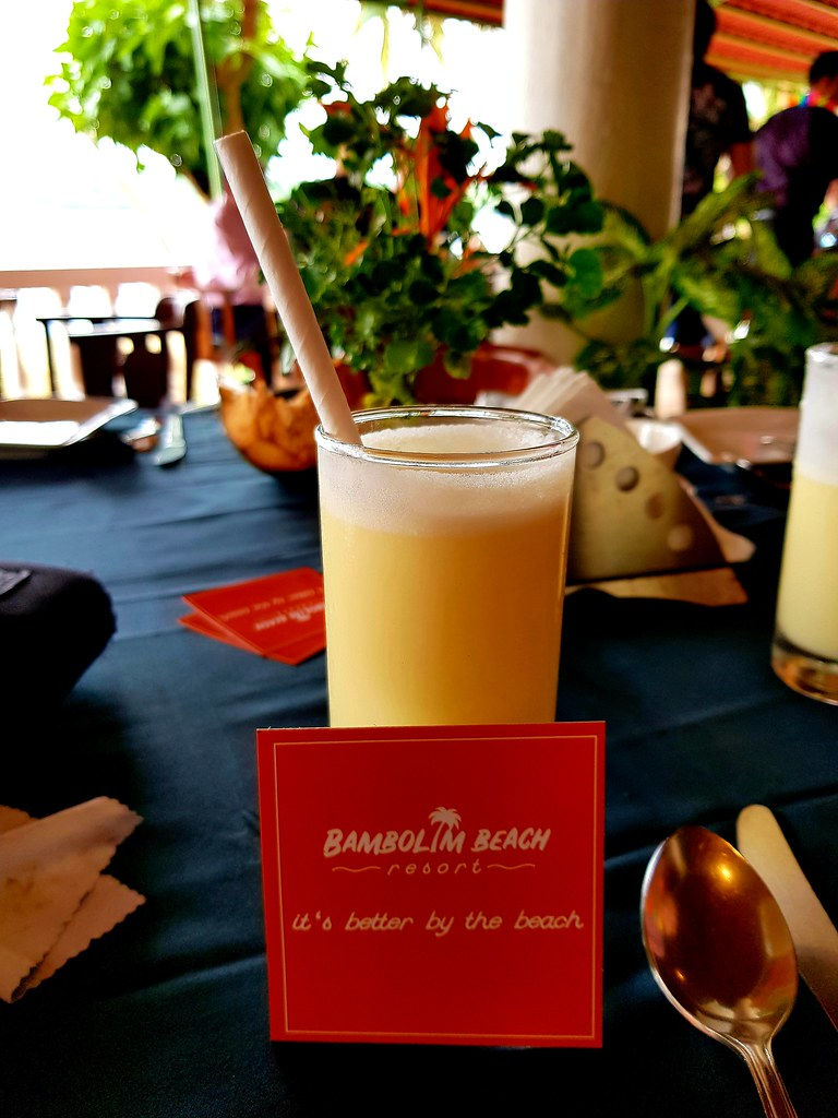 "A glass of mango lassi with a paper straw in it. In front of the glass there is a red label saying ""Bambolim Beach - It's better by the beach""."