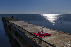 "Two wine glasses along with a wine breather carafe are patiently waiting to be filled on a wooden jetty by the sea in front of snow-capped Mt. Olympus, in Greece.  The pictorial presence of red wine is implied by the deep, saturated red colour.  The photograph was shot on the very first day of December 2019 at the Axios river's delta, near Kalochōri, Greece, by listening to the ""Red Red Wine"" masterpiece by UB40."