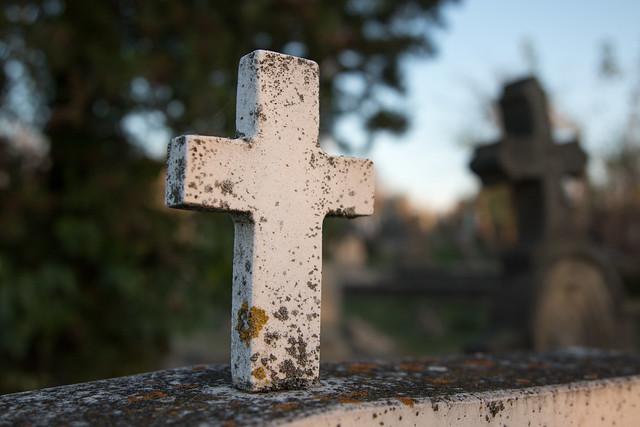 Weißes Kreuz auf einem Grabstein