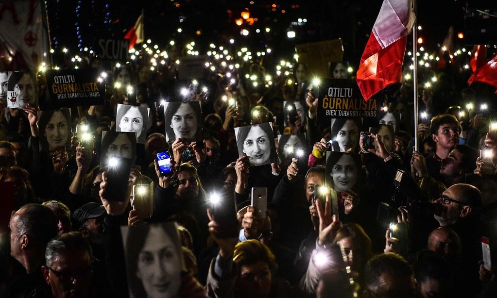 馬爾他民眾於總理辦公室外手持遭暗殺記者加利西亞照片。(圖片來源:AFP)