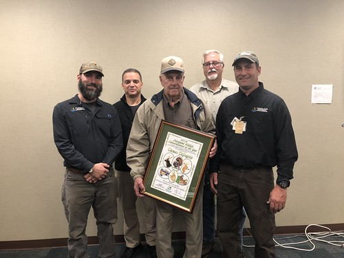 Photo of Wildlife and Heritage Service staff standing with Conservationist of the Year Thomas DiGregorio, displaying his framed award.=