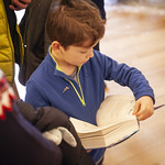 Young book fan reads while waiting to meet Tom Fletcher: © Robin Mair |