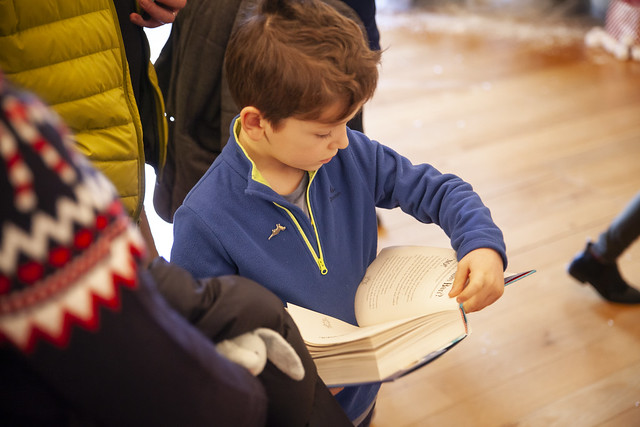 Young book fan reads while waiting to meet Tom Fletcher: © Robin Mair