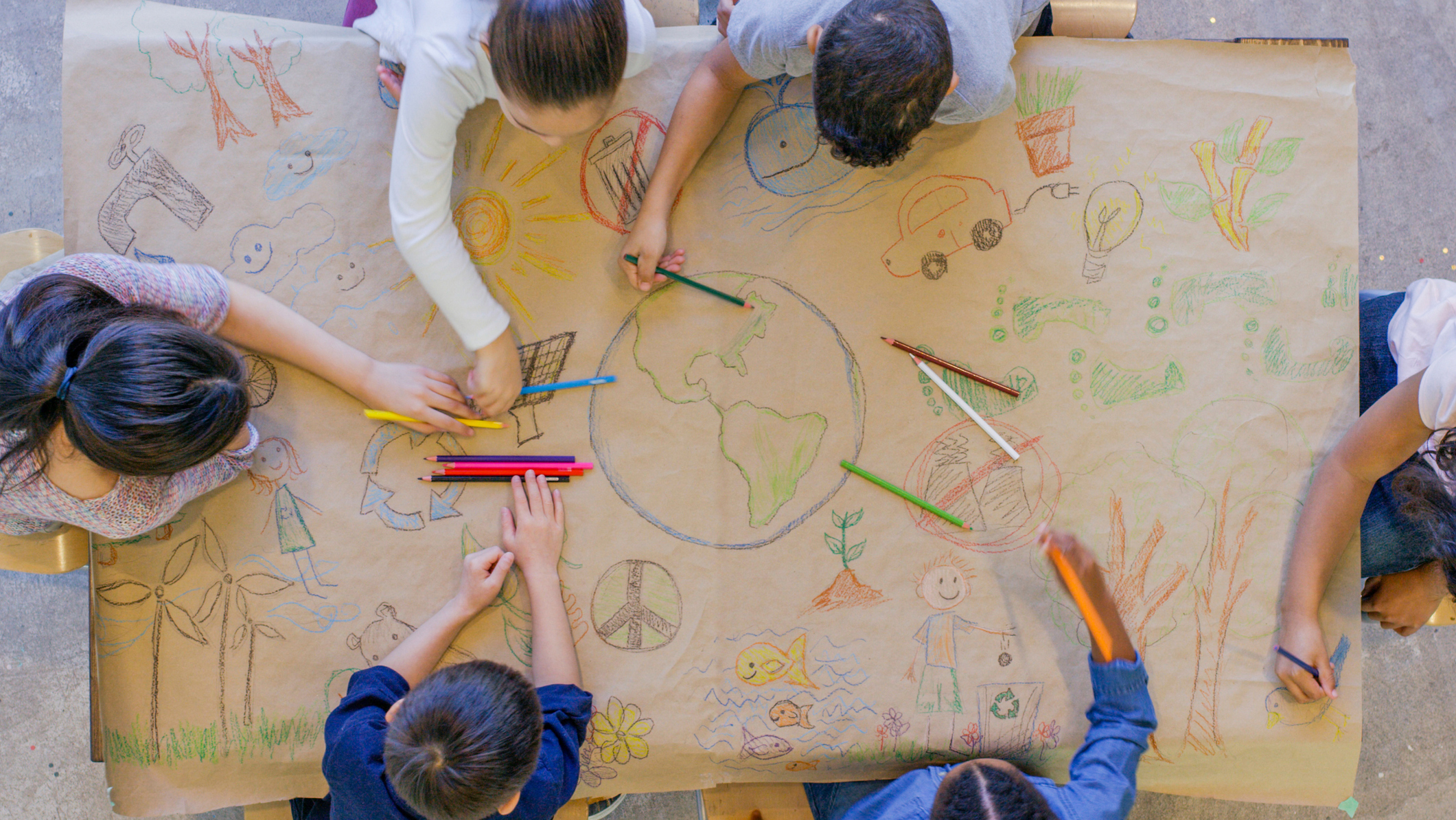 Children drawing pictures showing sustainability