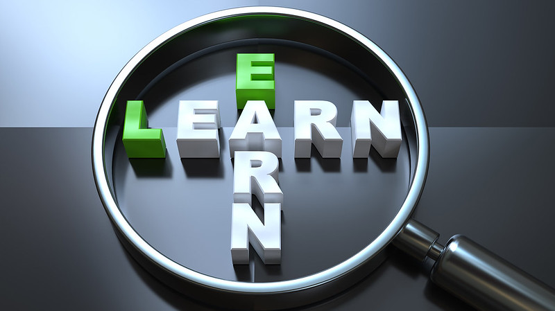 A magnifying glass on the words 'earn' and 'learn'
