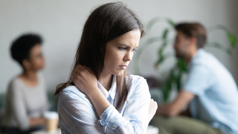 A teenager holding her painful shoulder
