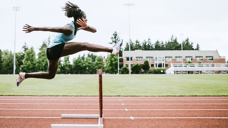 a female student in mid air jumping over a hurdle