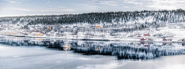 Icy waters and businesses and snow-covered homes along the edge of Alta Harbor, Norway-44a