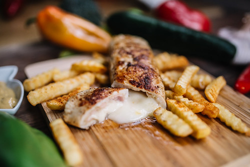 Tasty chicken steak with cheese and french fries on wooden table. Closeup of pickle cheese and fries.