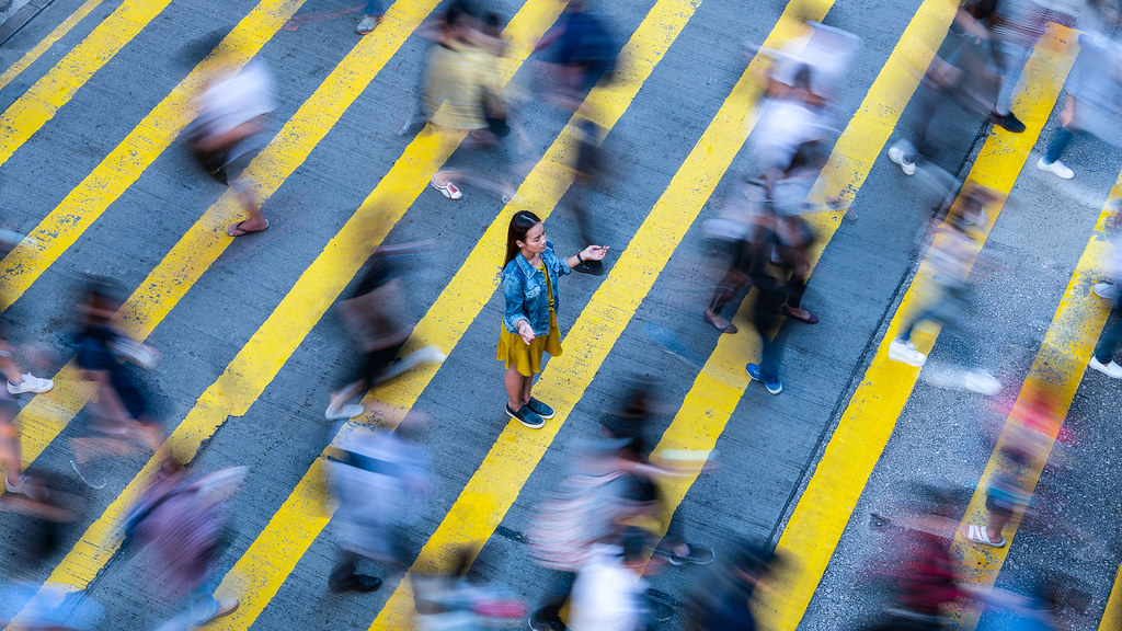 A calm woman standing in the middle of a busy crossing