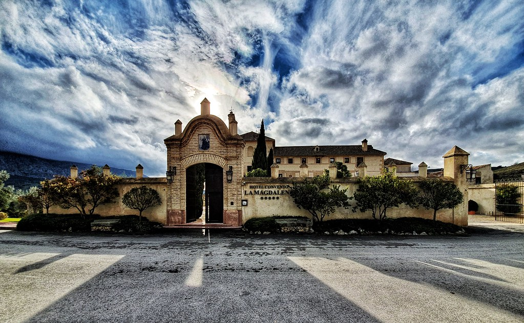 The entrance to the hotel La Magdalena which was once a convent. You can still see the towers behind the tall gate. The sky is very dramatic, with blue being observed through the clouds.
