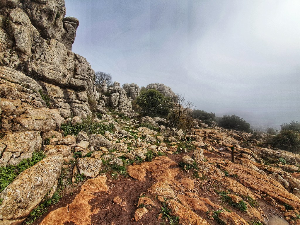 The photo is dominated by a big rock on the right and a path passing through a rocky terrain on the left. The front of the photo is foggy. The path is muddy and brown.