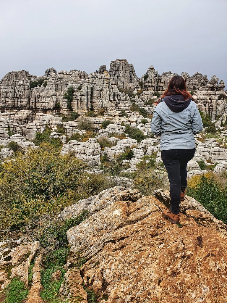Joanna standing with the back at the photo, looking towards the rock formations. She is wearing a gray jacket, a black hoodie, black jeggins and brown hiking boots.