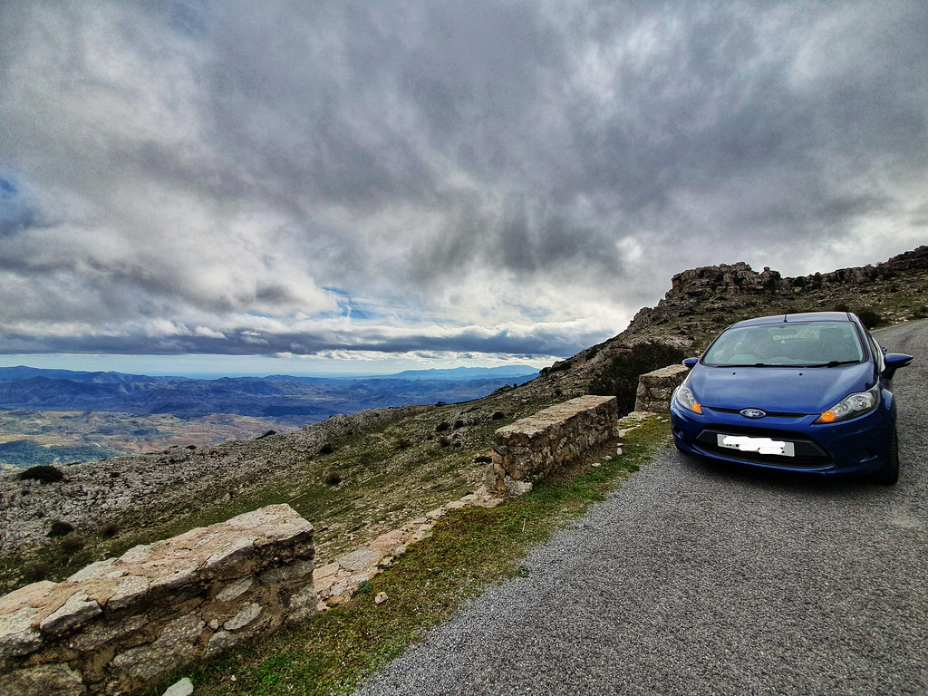 A blue car parked on the side of a narrow mountain road. On the right hand side of the photo you can see the panorama stretching all the way to the sea, which is 45 kilometers away. The sky is filled with clouds but over the sea is clear.
