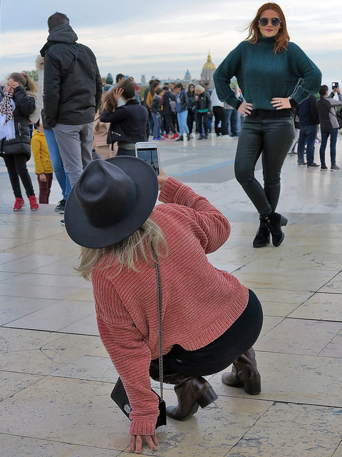 Photographer in precarious balance taking the picture of her friend