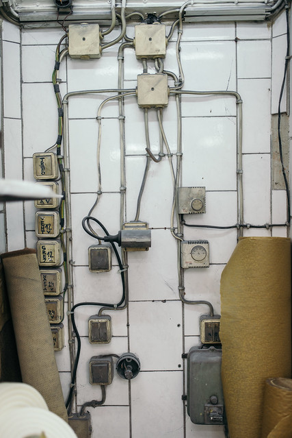 Old electrical cable wires and boxes on a white ceramic wall in a car workshop. Make-shift electrical wiring