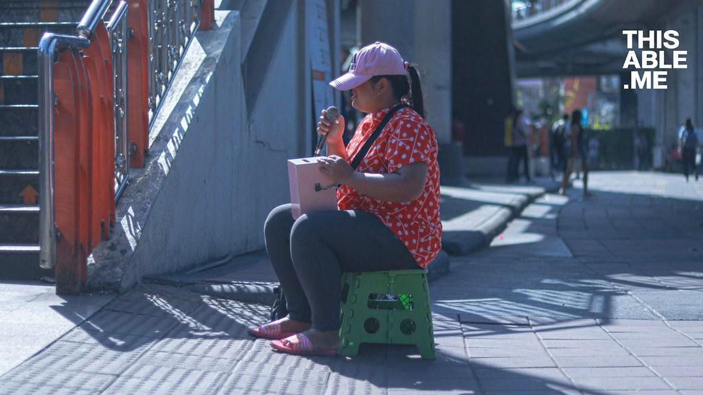 รูปพี่จีใส่หมวกนั่งร้องเพลงอยู่ข้างสะพานลอย