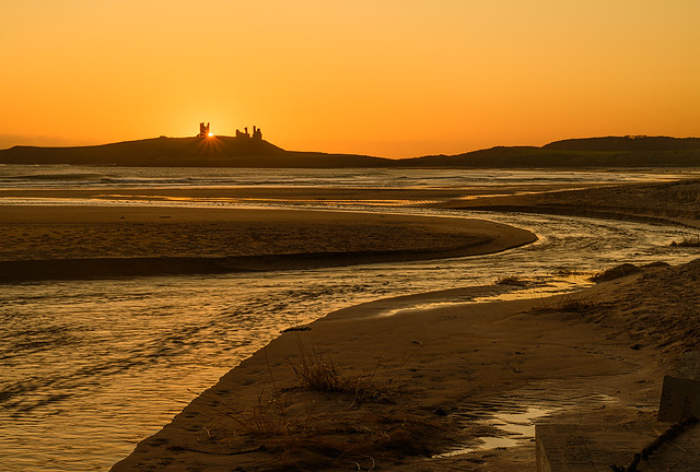 Sunrise captured from Embleton beach looking towards Dunstanburgh Castle in Northumberland. I love the stream S bend taking the eye upto the sun rising behind the castle ruins.