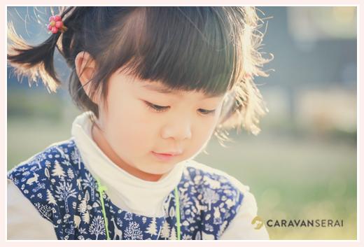 野原で遊ぶ女の子の顔のアップ 夕方の西日