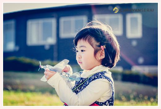 飛行機好きの女の子 おもちゃの飛行機を持って飛ばすところ