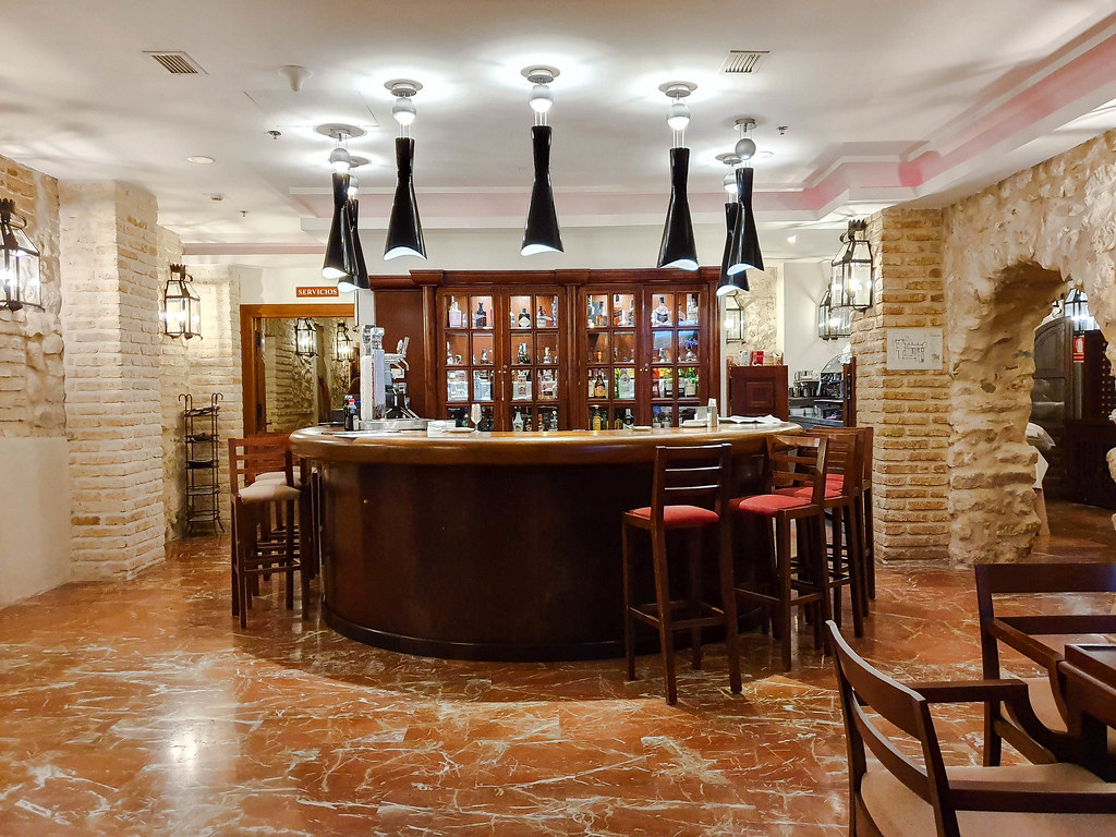 The lobby bar, round, made out of dark brown wood. It has several tall chairs with red cushions around it. The walls on the right and left are exposed brick, in a sandy color.
