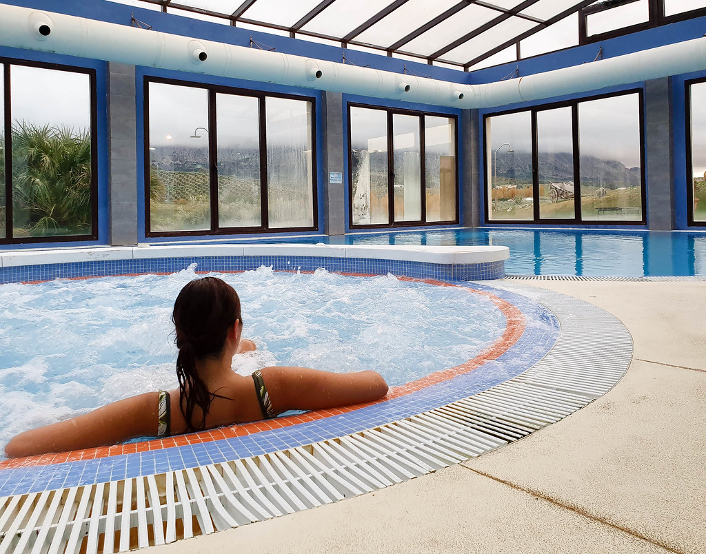 A woman wearing a green bathing suit relaxing in a jacuzzi, in the spa. Around there are panoramic windows.