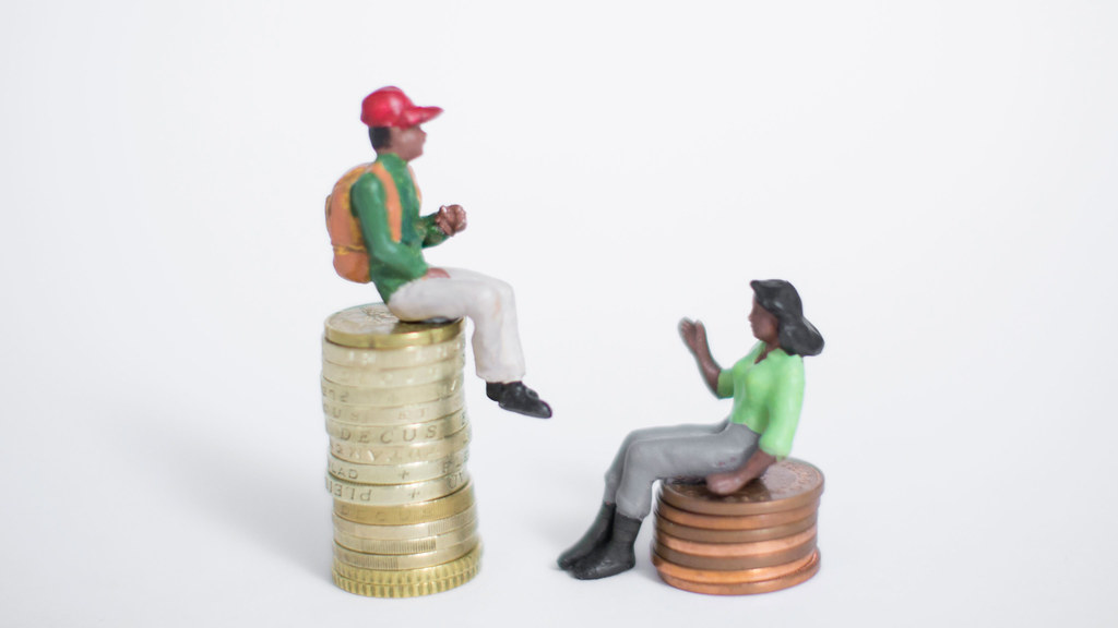A model of a man and a woman on different piles of money illustrating inequality.