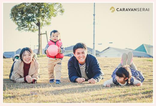 公園の芝生に寝転んで家族写真 西日が当たる秋の公園