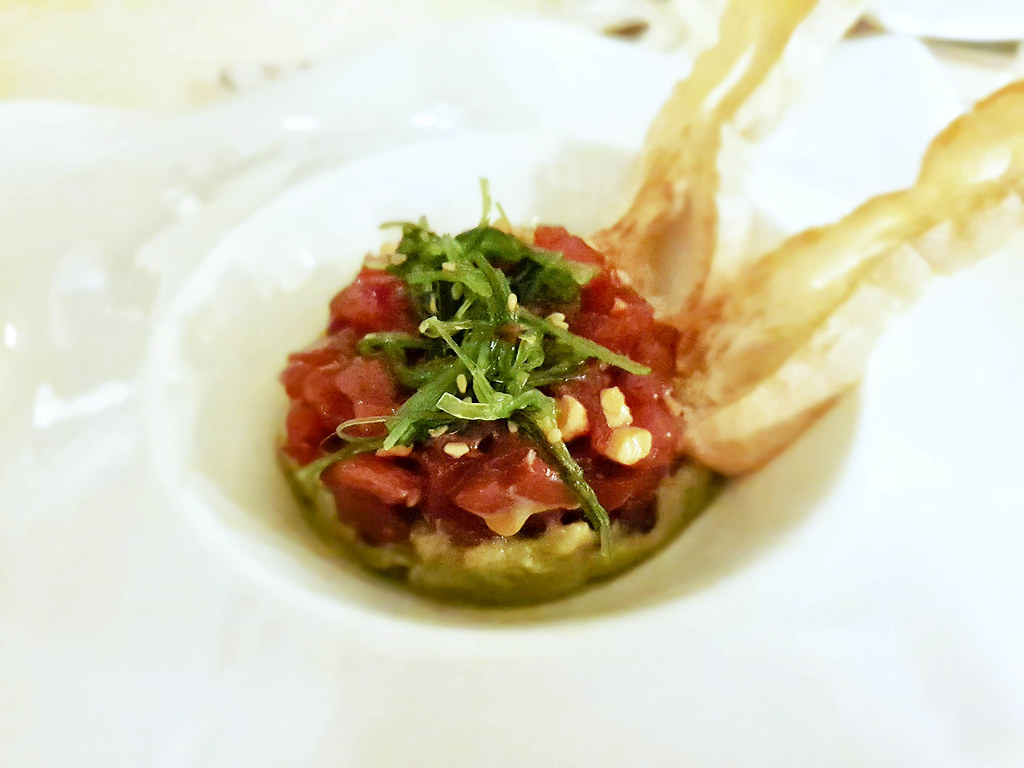 A plate with green avocado mouse at the bottom, red tuna tartar on top and green leaves decorating.