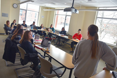 Jeanne McCaffery (teal sweater in the back right corner) and allied health students listen to student presentations in the Honors section of Research Methods in Allied Health.