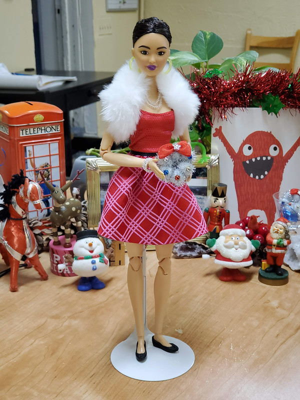 I stole the outfit from a blond holiday Barbie who has joined the stack of nude unused dolls.