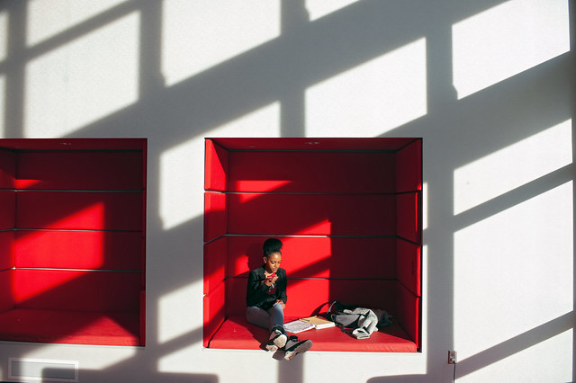 Student sitting in red wall inset in Student Success Center