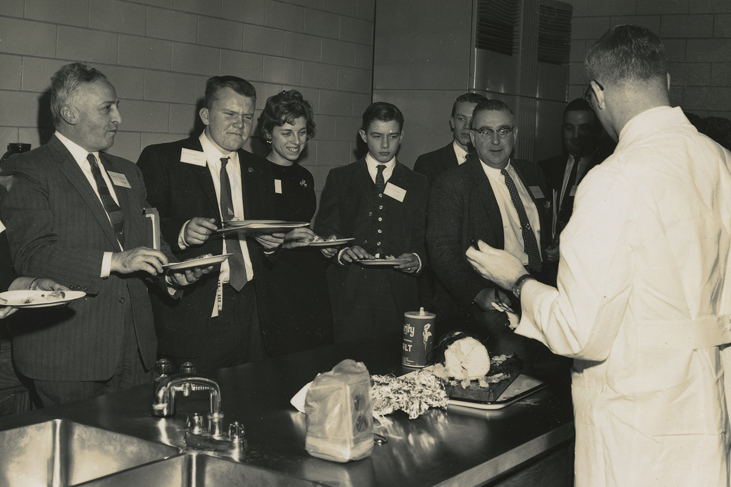 A group of people sampling food in front of a man in a lab coat.