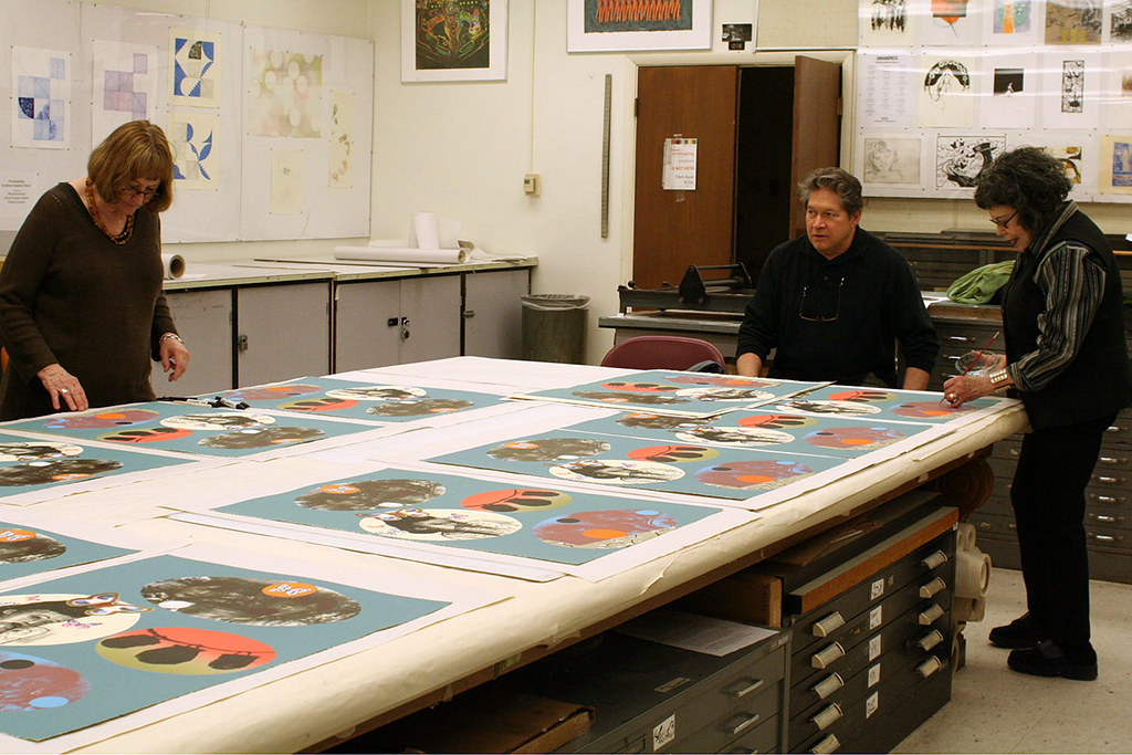 Phyllis Bramson and visitors review prints